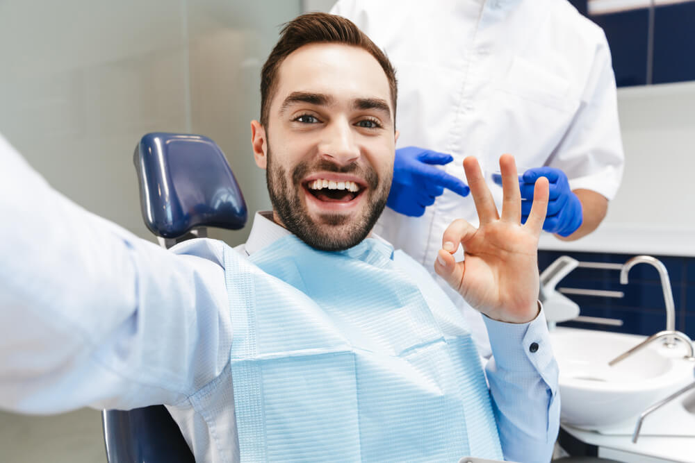 Image of brunette young man sitting in dental chair at medical center and smiling