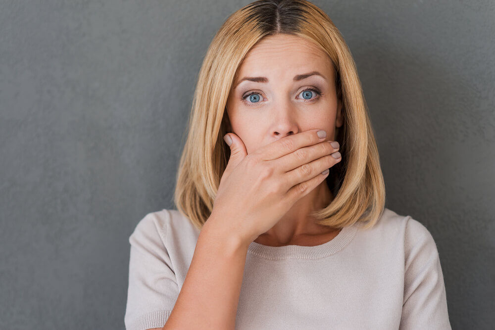 Shocking news. Surprised mature woman covering mouth with hand and staring at camera